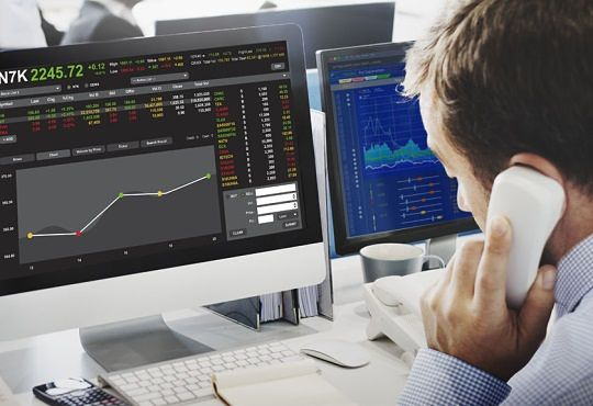 Active Investing and Speculation Management Strategies - picture of stock investor sitting at his desk using the phone talking to his broker about Speculation Trading while looking at his computer