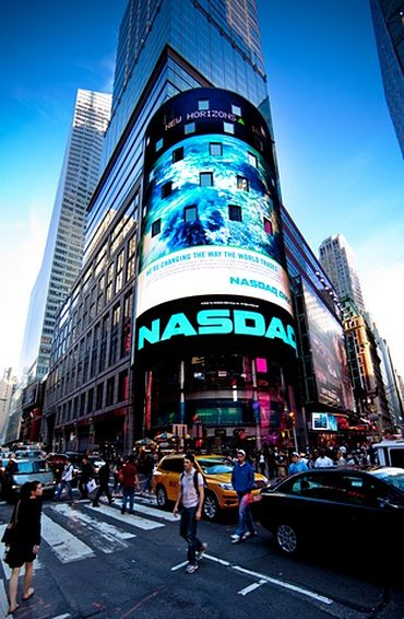 An Introduction to Stock Investing - Stock Market basics part 1; Picture of the NASDAQ stock market building located in the city with lots of investors walking past.