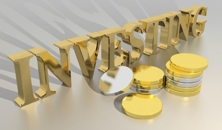 An Introduction to Stock Investing - Stock Market basics part 2; Picture of a beginner investing sign showing gold coins on a beige colored background panel.