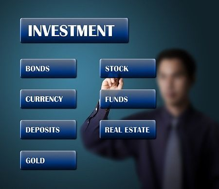 An Overview of Investing - The Reluctance to Invest; Picture of more investment options for stock investors such as stocks funds and bonds on panels against a glass wall.