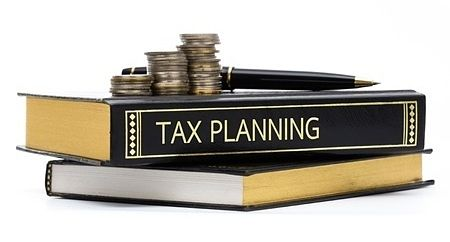 An Overview of Investing - Tax Considerations for Stock Investors; Picture of a tax planning book with a black cover and silver coins on top for stock investors.