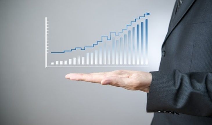 An Overview of Investing Strategies - Growth Investing; Picture of a stock Investor placing his left hand under a growth chart displayed on a clear glass panel hanging in space.