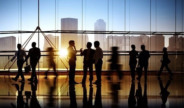 Stock Market Business Basics - Business Types; picture of lots of business men standing in an office area discussing the company profits over the last year
