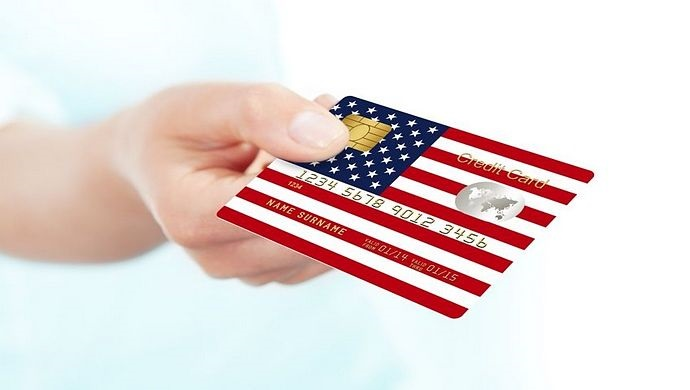 Profits and the Economy - businesses economy; picture of the United States of America shown on a credit card with an investor handing it over for payment