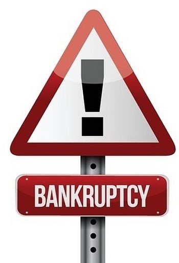 Buying Stocks while in Bankruptcy; picture of a road sign with triangle shape with bankruptcy written on it with exclamation mark in large white capital letters on a red background