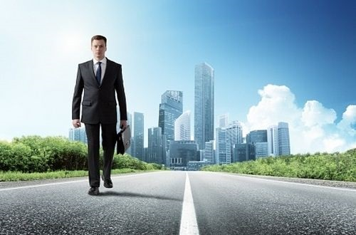 Bond Categories - Corporate Bonds; picture of an investor walking away from the  city on a highway road carrying a business briefcase on a blue sky sunny day