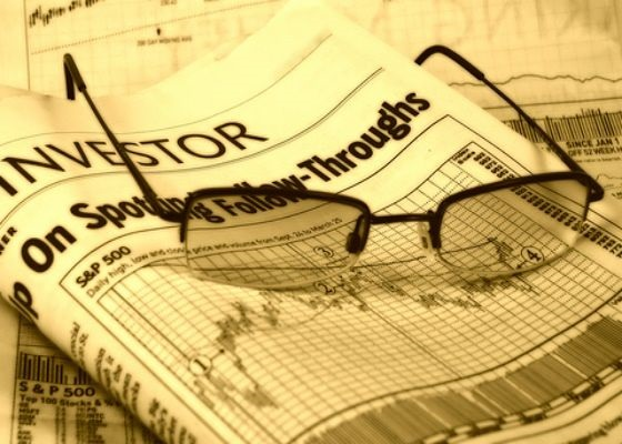 Swing Trading - Creating the List; picture of a newspaper with financial pages shown with stock chart and a pair of glasses and the display is in gold colored black and white photo style