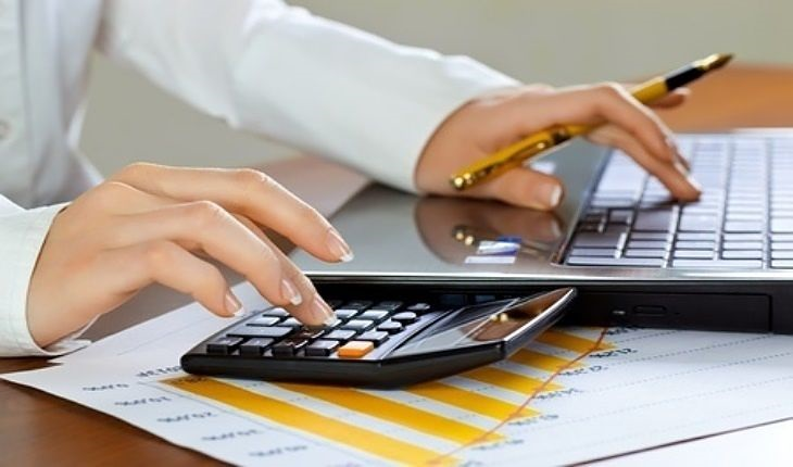 growth investing - Finding Good Growth Stocks; picture of investor working on tablet checking earnings and revenue data with a calculator looking for growth trend on bar chart