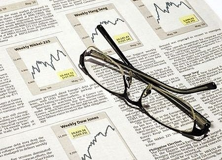 Selecting a Fund screener - picture of financial newspaper with the fund charts for prices to buy with a pair of glasses left on the page by an investor