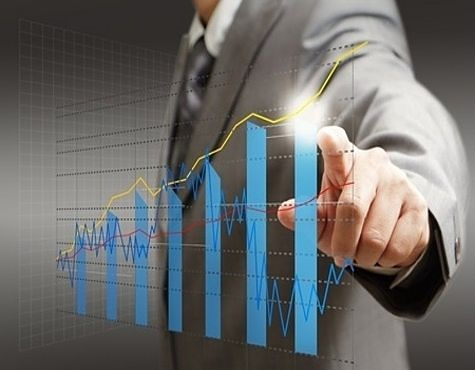 Growth Investing - Growth Stocks that Stop Growing; picture of investor pointing at earnings and revenue chart on a glass panel mounted on the wall
