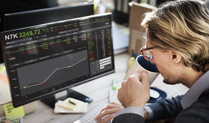 How to Invest in Stocks - Should You Trade; Picture of a beginner stock investor sitting at his desk while drinking a cup of coffee and looking at stock charts on a computer screen.