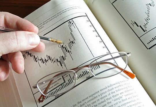 Active Investing and Speculation Management Strategies - picture of a stock investor holding a pen while pointing at a stock chart in a text book on Market Volatility