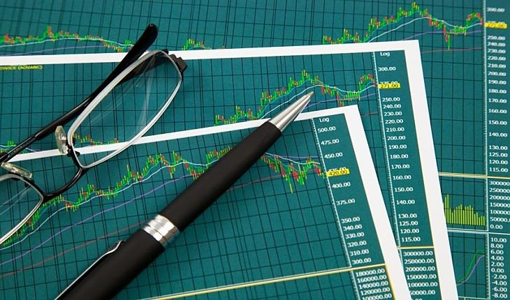 Introduction to Chart Patterns - picture of three stock chart sheets showing various chart patterns with a pen on top and glasses to help spot trends for traders and investors to profit from a trade