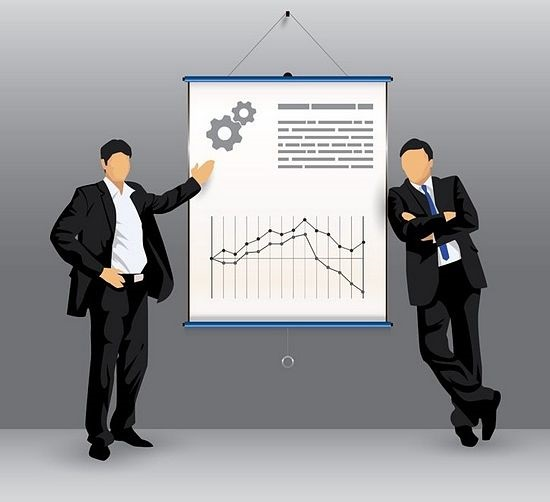 Introduction to Trade Management- picture of two stock traders looking at a stock chart on a wall poster analyzing the trade management for their position