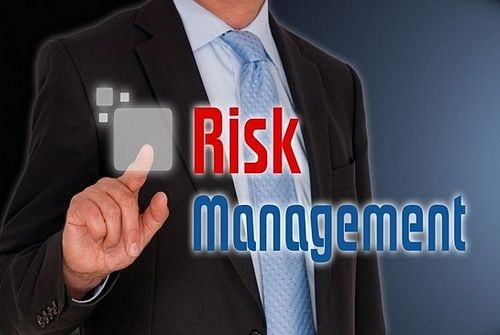 Introduction to Trade Management - picture of a stock trader pointing at a risk management sign on a glass panel on the wall written in large font capital letters in red and blue
