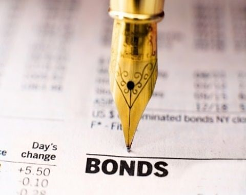 Understanding Bonds - Investing in Bonds; picture of a pen pointing at prices printed in the financial newspaper for investors to select for their portfolio