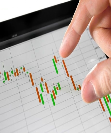 Understanding Stock Options - Option Behavior and the Greeks; picture of an investor examining a stock chart with bars in green and red on a computer screen
