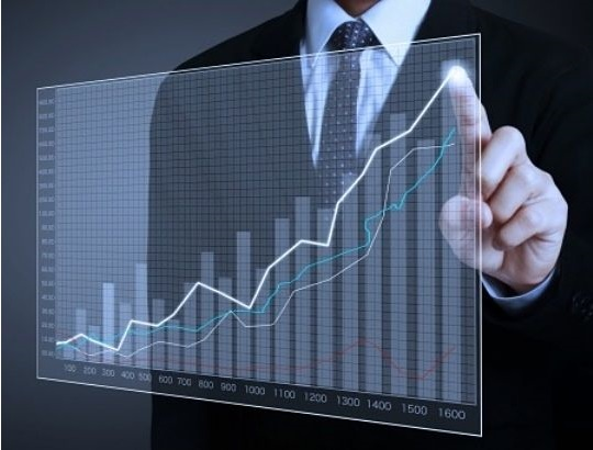 Investing in Stocks for Beginners - profit taking; picture of a stock investor pointing at the top of a chart displayed on a glass panel floating in front of him using his index finger