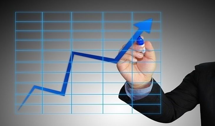 trade management profit target - picture showing a stock trader pointing to an uptrend line with an arrow plotted on a grey background for the profit target with light blue grid lines on a light grey background