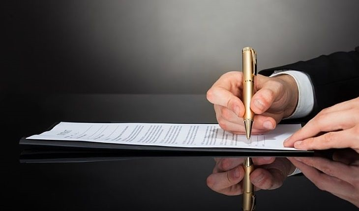 Understanding the Financial Statements - Reading the 10-K company report; picture of an accountant signing the 10k company report for an investor to build their portfolio