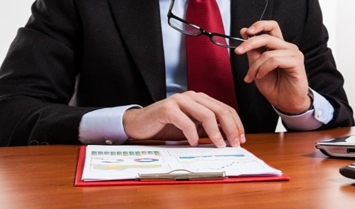 Understanding the Financial Statements - Reading the 8-K company report; picture of an investor reading the 8k company report for a stock portfolio