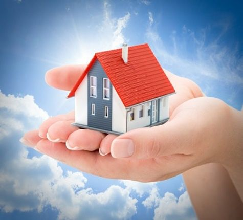 An Overview of Investing - Real Estate Investment Trusts; Picture of a model house with an investors hand holding the house in their hands against the blue sky with clouds.