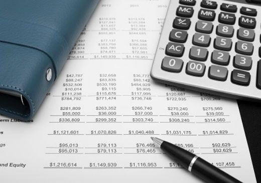 Understanding the Financial Statements - Reporting; picture of the financial statements printed out on paper with a calculator on top of paper sheets with a pen