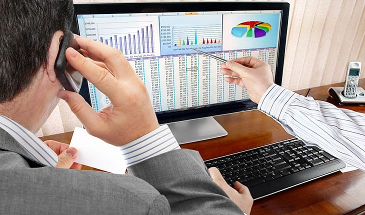 Active Investing and Speculation Management Strategies - picture of stock investor using a computer to check stock price data on the screen with charts while sitting at his desk