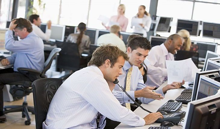Investing in Stocks for Beginners - Portfolio size and Brokerage costs; picture of lots of stock brokers working in an office building placing orders for their clients investment portfolios while using the phone and computer