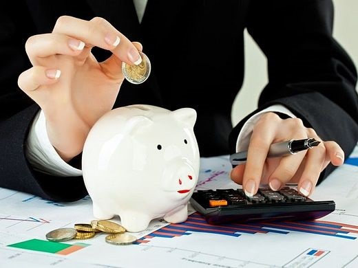 An Overview of Investing - Saving for your Investments; Picture of a man saving money in a piggy bank for his future investments while using a calculator.