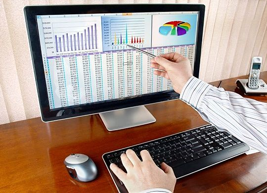 building wealth with passive investing - picture of an investor using a computer screen to help him in Selecting Stocks Funds and funds while sitting on a brown wooden top table