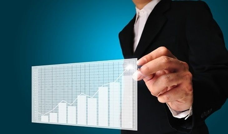 Speculative Investing Strategies - Small-Cap Growth Stocks; picture of an investor pointing to stock chart that is trending higher with a pen in his hand