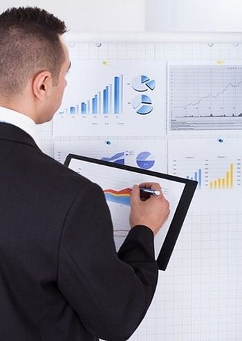 The Investing Style of Peter Lynch; Picture of a stock investor checking the market data on his clipboard using a pen and examining the charts and data shown on a wall poster.