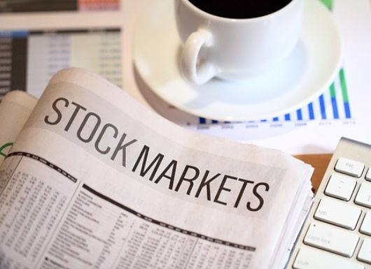 Stock Investing Part 1 - Stock Classes; Picture of stock prices shown on a financial newspaper market page for investors laying on the table with a cup of coffee and a bar chart.
