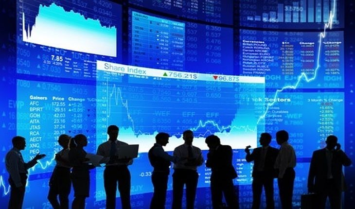 Stock Investing Part 1 - Market Capitalization; Picture of a group of stock investors in a conference discussing the stock prices shown in front of a large wall mounted panel Market board.