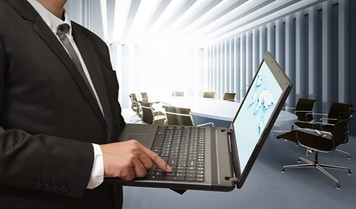 Stock Investing Part 2 - Industry Insiders; Picture of a stock investor using a laptop in an office boardroom with high back office chairs to analyze the stock chart shown by the insider.