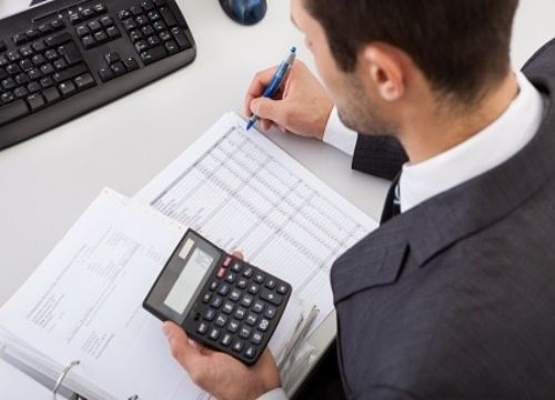 Stock Investing Part 2 - Industry Insiders; Picture of a stock investor sitting at a desk using calculator for to analyze the stock price data to check the profitability of their investment portfolio.