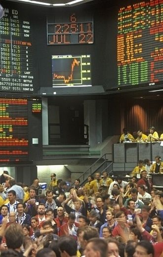 trade management stock order types - picture of the stock exchange floor with traders placing orders to buy and sell stock for clients