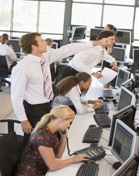 trade management stock order types - picture of several stock brokers placing orders on their phones and via the computer in a brokers office building