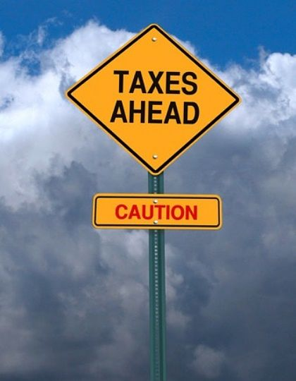 An Overview of Investing - Tax Considerations for Stock Investors; Picture of a road sign with yellow background and black writing saying tax caution sign for stock investors