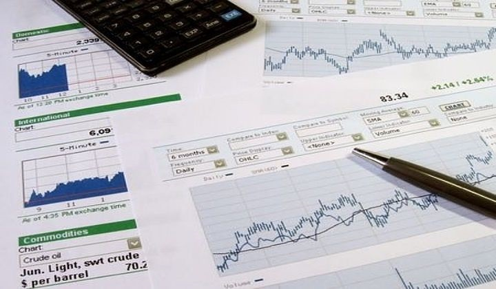 Technical Analysis - the bar chart; picture of several bar charts drawn on paper sheets for the stocks to conduct a technical analysis by using a calculator and pen for stock traders