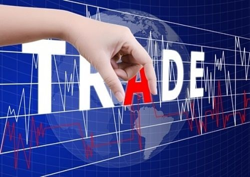 Day Trading - picture of a stock chart with a bright blue background with the word trade in large font white capital letters across the screen width with the letter A in red