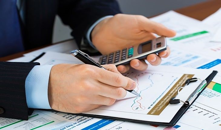 Dividend Investing - The Dividend Investor; picture of man viewing stock chart with calculator in hand examining the dividend data to check the yield for returns
