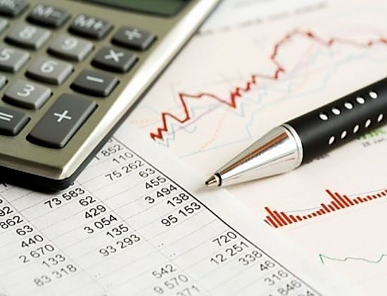 Dividend Investing - The Dividend Investor; picture of calculator on top of stock chart and data with a black pen laying beside it