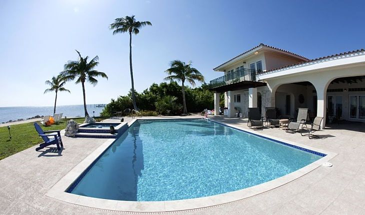 The Investing Style of John Templeton - The Life of John Templeton; Picture of a wealthy stock investors white mansion house with a swimming pool and palm trees on a beach front property.