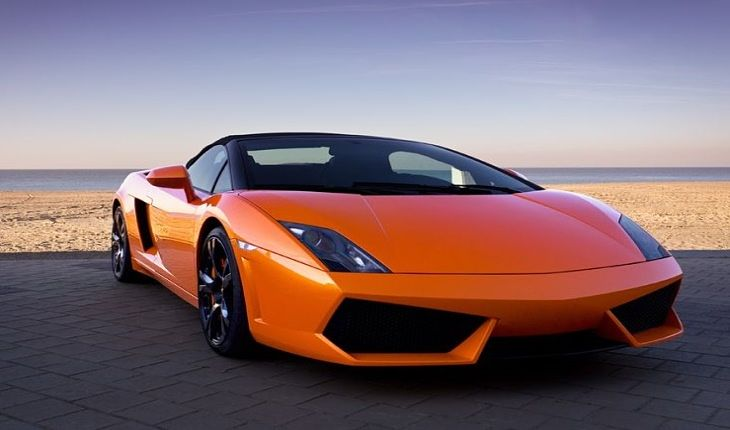 The Investing Style of Peter Lynch - The Life of Peter Lynch; Picture of a wealthy stock investors bright orange sports car parked at the beach car park with sand and the water behind.