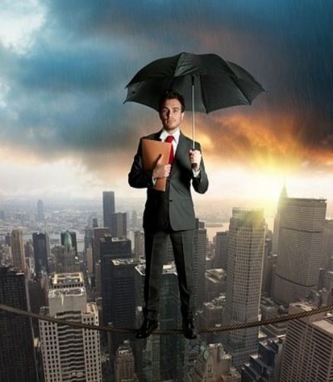 The Investing Style of Warren Buffett; Picture of a stock investor holding an umbrella over his head to symbolize protection from any adverse market conditions that may occur for the risk.