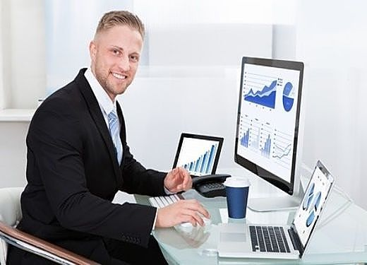 Investing in Stocks for Beginners - Portfolio size and Brokerage costs; picture of a stock broker sitting at a desk while using a computer to check the portfolio and brokerage costs for their clients