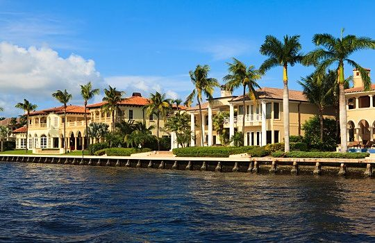 The Investing Style of George Soros - The Life of George Soros; Picture of wealthy stock investors mansion houses situated along a water channel as water front homes with palm trees.