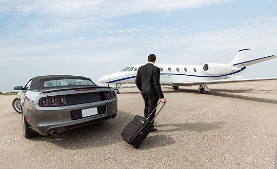 The Investing Style of Warren Buffett - The Life of Warren Buffett; Picture of a wealthy stock investor walking across the tarmac leaving his car and boarding a private jet plane.